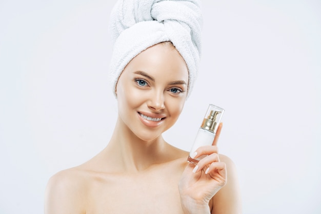 Beautiful smiling woman poses with cosmetic product