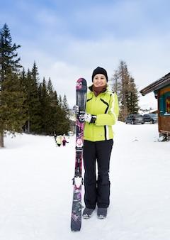 Красивая улыбающаяся женщина позирует на вершине склона с лыжами