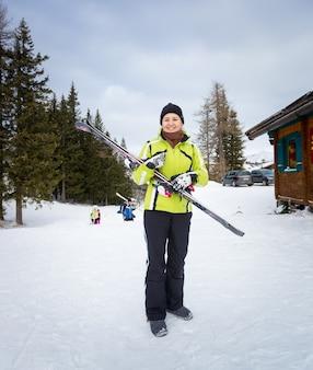 Красивая улыбающаяся женщина позирует с лыжами на склоне