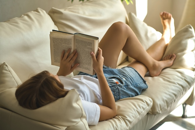 Beautiful smiling woman reading a book at home