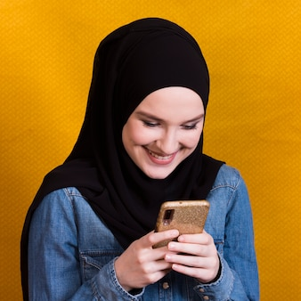 Beautiful smiling woman reading messages on smartphone over yellow backdrop