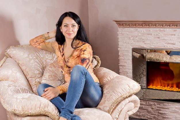 暖かい火の前で快適な布張りのアームチェアで彼女のジーンズとスタイリッシュなトップでリラックスした美しい笑顔の女性