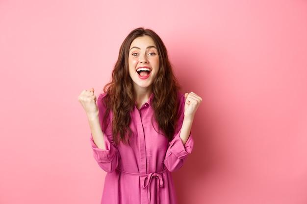 美しい笑顔の女性は、幸せで興奮した顔で悲鳴を上げ、「はい」と言って、ガッツポーズを作り、勝利し、チャンピオンのように感じ、勝利し、ピンクの壁の上に立っています。