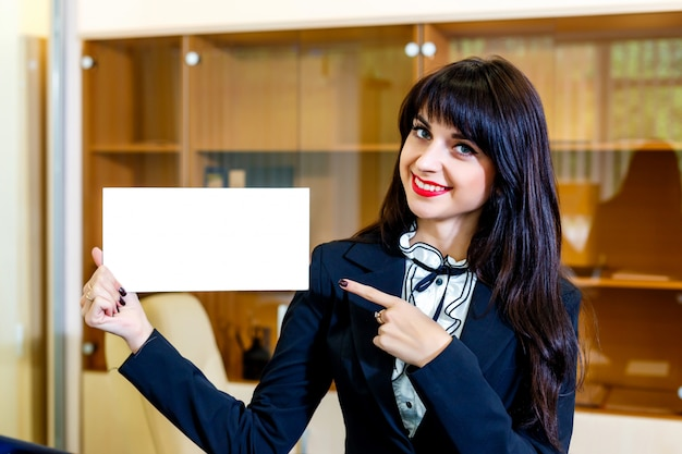 Beautiful smiling woman shows empty card in office