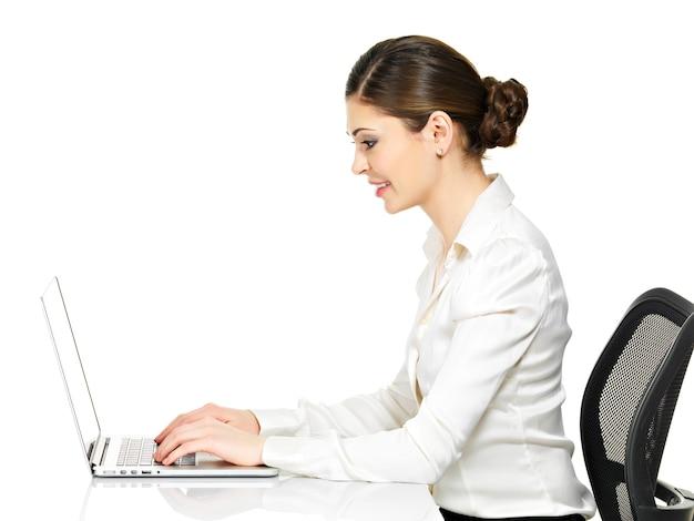 Красивая улыбающаяся женщина сидит за столом и работает на ноутбуке в белой рубашке - изолированной на белом.