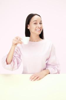ピンクのスタジオに座って、コーヒーを手に持って幸せそうに見える美しい笑顔の女性。ミニマリズムスタイルのクローズアップトーンの肖像画