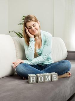 ソファに座って「家」という言葉を見ている美しい笑顔の女性