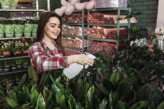 Красивая улыбающаяся женщина опрыскивает растения в своем садовом центре