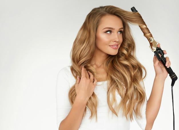 健康的な長いブロンドの髪をまっすぐにする美しい笑顔の女性