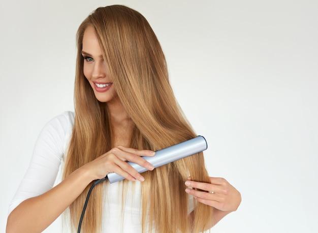 Красивая улыбающаяся женщина выпрямляя здоровые длинные светлые волосы