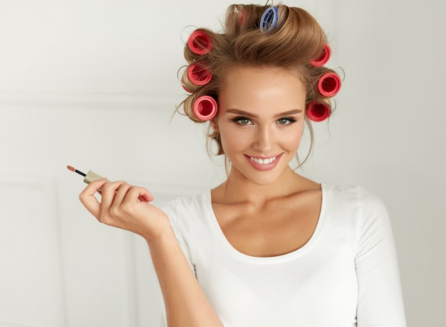 健康的な長いブロンドの髪をまっすぐにする美しい笑顔の女性 Premium写真