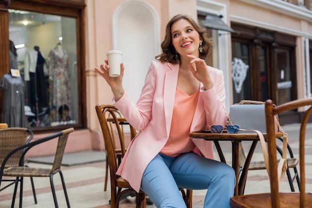 Bella donna sorridente in abito elegante seduto a tavola indossando giacca rosa, romantico stato d'animo felice, data in caffetteria, tendenza moda primavera estate, bere caffè, fashionista