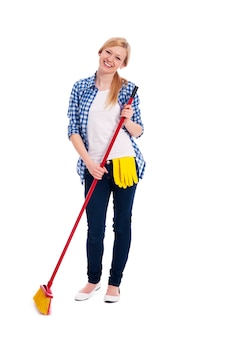 Beautiful and smiling woman sweeping the floor