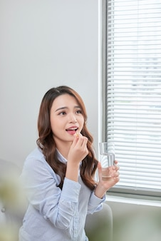 비타민 알 약을 복용 하는 아름 다운 웃는 여자. 건강 보조 식품