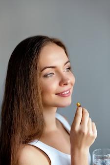 비타민 알 약을 복용하는 아름 다운 웃는 여자