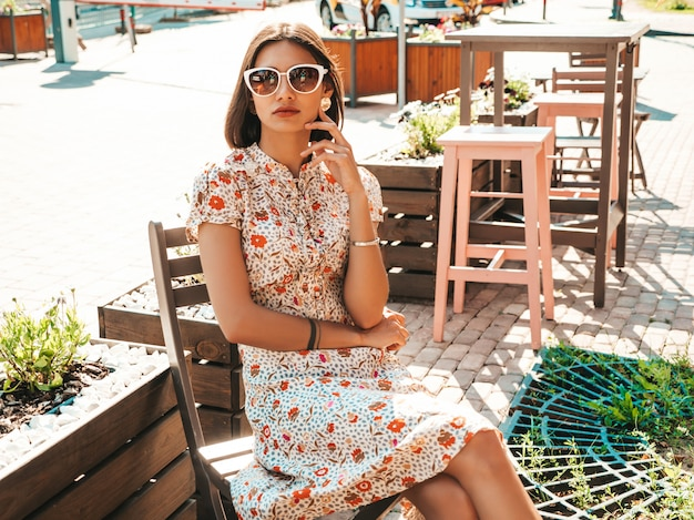 Beautiful smiling woman in trendy summer sundress sitting in a cafe