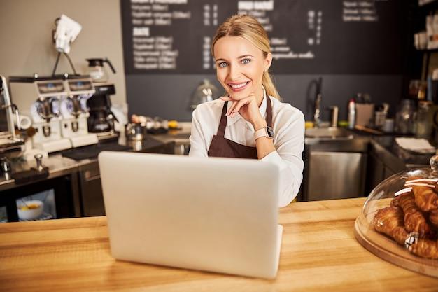 노트북 카페에서 일하는 아름다운 웃는 여성 웨이터