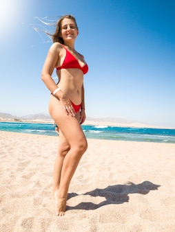 Beautiful smiling woman wearing red thongs and black bikini posing on the sea beach at bright sunny day against ocean waves. girl relaxing and having good time during summer holiday vacation.