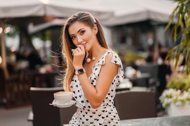 カプチーノのカップとストリートカフェに座っているスタイリッシュな白いプリントドレスを着て美しい笑顔の女性