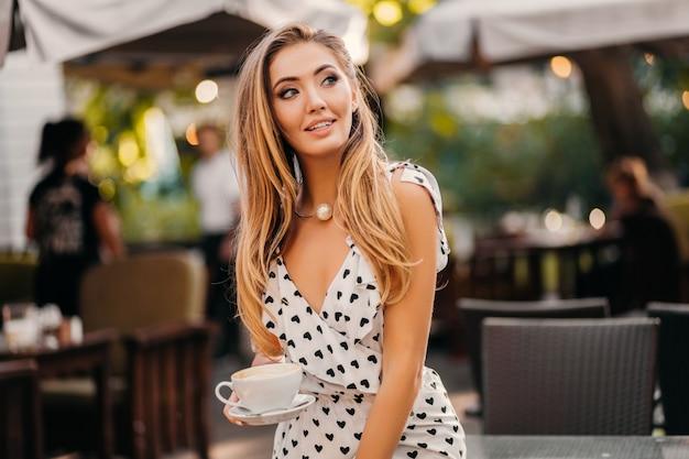 Bella donna sorridente che porta vestito stampato bianco alla moda che si siede nel caffè della via con la tazza di cappuccino