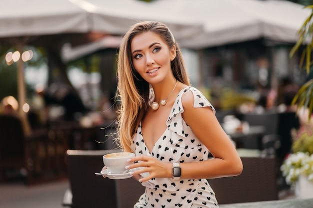 Beautiful smiling woman wearing stylish white printed dress sitting in street cafe with cup of cappuccino