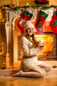 Beautiful smiling woman in white sweater warming at fireplace with hot tea