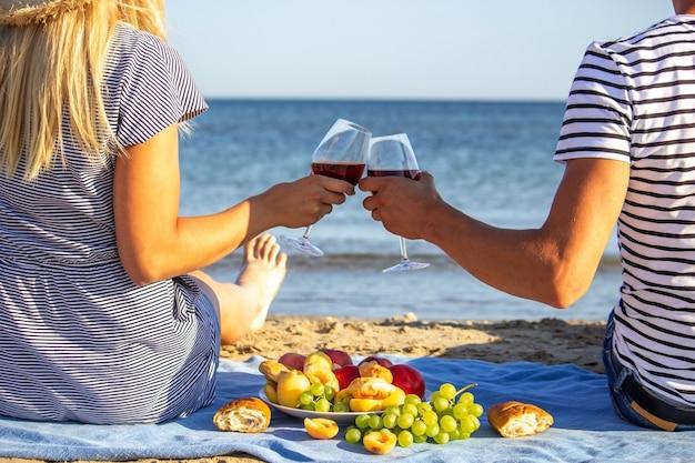 해변에서 와인 한 잔과 함께 아름 다운 웃는 여자. 과일 레드 와인. 선택적 초점입니다.