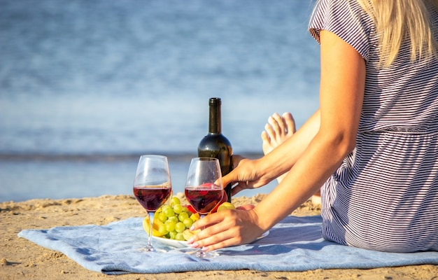 해변에서 와인 한 잔과 함께 아름 다운 웃는 여자. 과일 레드 와인.