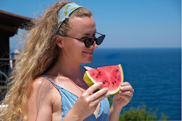 海の景色の休日の夏を見て水着を着てスイカのスライスを持つ美しい笑顔の女性。