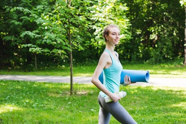 Красивая улыбающаяся женщина с ковриком для йоги на открытом воздухе