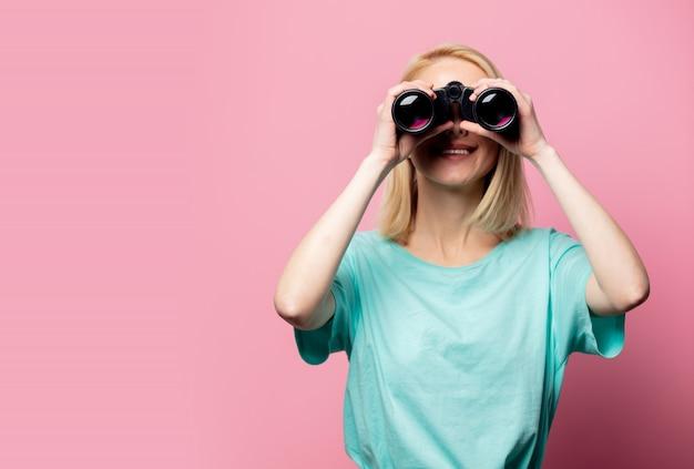 Beautiful smiling woman with binoculars on pink wall