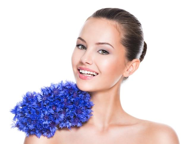 Bella donna sorridente con fiori di campo blu