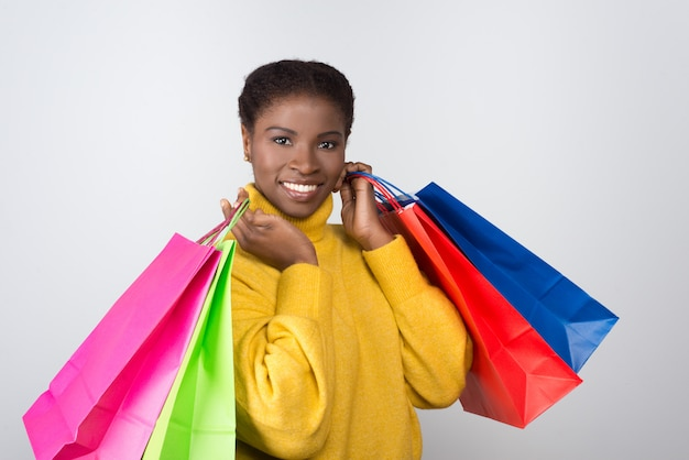 Beautiful smiling woman with colorful shopping bags on shoulders
