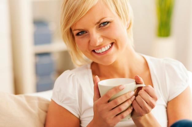 Donna bella e sorridente con una tazza di caffè