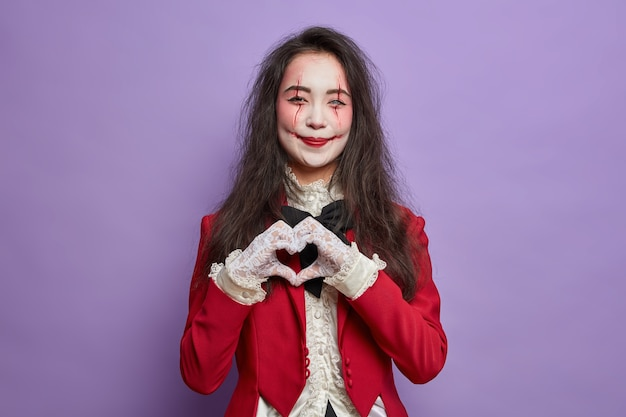 Beautiful smiling woman with fearful makeup pale ghost face and bloody scars makes heart gesture and expresses love being on halloween party isolated over purple wall