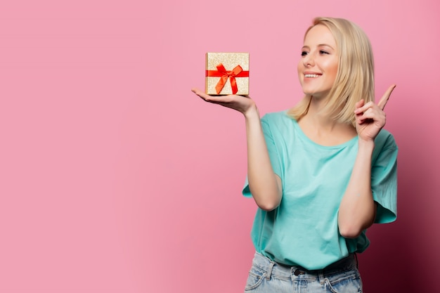 Beautiful smiling woman with gift box on pink wall