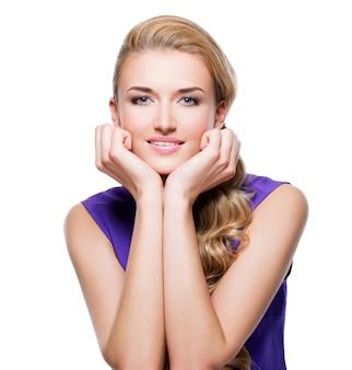 긴 금발 곱슬 머리와 얼굴-흰 벽에 고립 근처 손으로 아름 다운 웃는 여자.