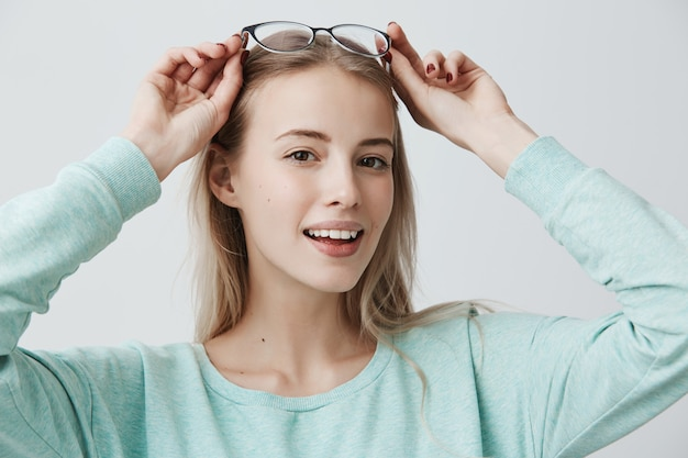 Beautiful smiling woman with long blonde hair and stylish eyewear, has european appearance, looks delightfully