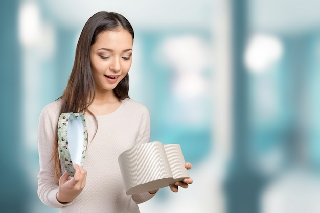Beautiful smiling woman with long hair holding gift box