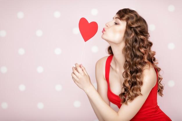 聖バレンタインデーのための赤いハートの美しい笑顔の女性