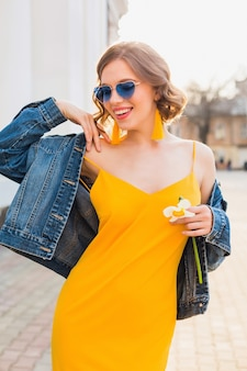 Beautiful smiling woman in yellow stylish dress wearing denim jacket, trendy outfit, spring summer fashion trend, sunny, happy mood, blue sunglasses, street fashion