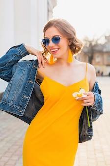 Bella donna sorridente in vestito elegante giallo che indossa giacca di jeans, vestito alla moda, tendenza moda primavera estate, umore soleggiato e felice, occhiali da sole blu, moda di strada