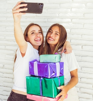 Beautiful smiling women with birthday gift in front of brick wall
