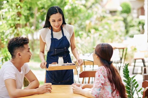 Beautiful smiling young asian waitress bringing tray with breakfast to young happy couple sitting at table in outdoor cafe