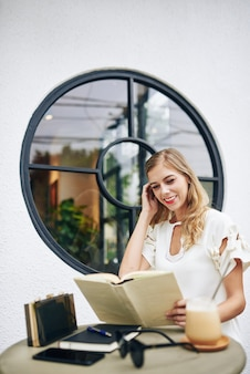 Beautiful smiling young blond woman reading funny story in thick book when resting at outdoor cafe