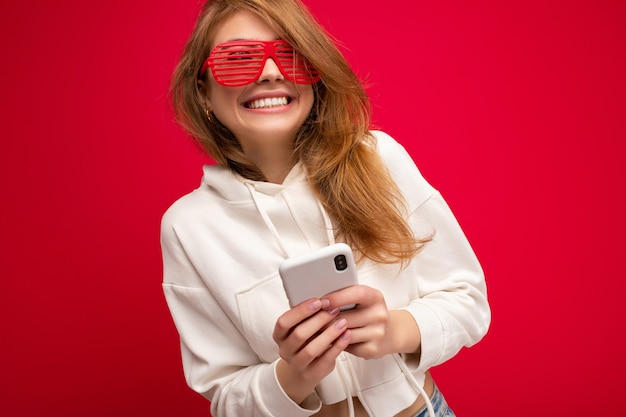 スタイリッシュな白いパーカーと面白いカラフルなメガネを身に着けている美しい笑顔の若いブロンドの女性