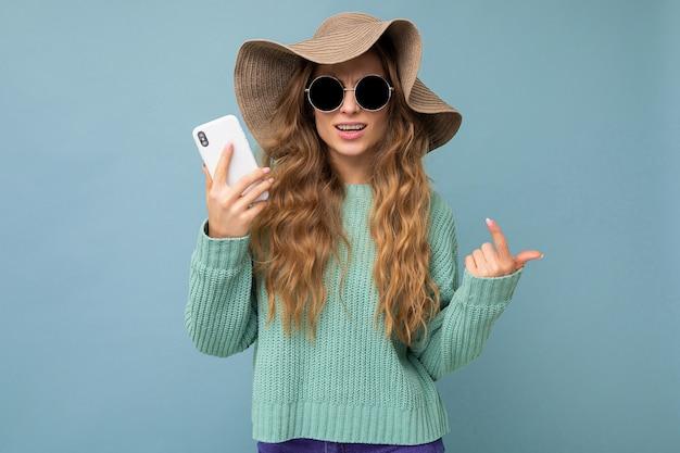 카메라를 바라보는 스마트폰을 들고 복사 공간이 있는 배경에 격리된 선글라스와 모자를 쓰고 웃고 있는 아름다운 젊은 금발 여성.