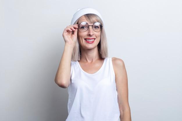 明るい背景に眼鏡をかけて美しい笑顔の若いブロンドの女性。
