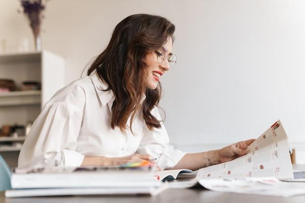 Красивая улыбающаяся молодая брюнетка женщина учится, сидя в кафе в помещении, делая заметки, читая
