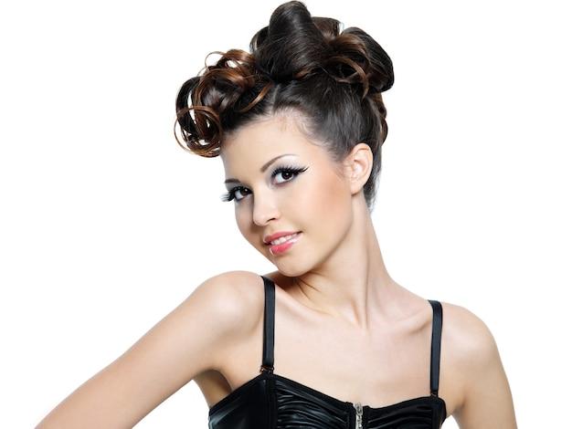 Bella giovane donna bruna sorridente con l'acconciatura di moda